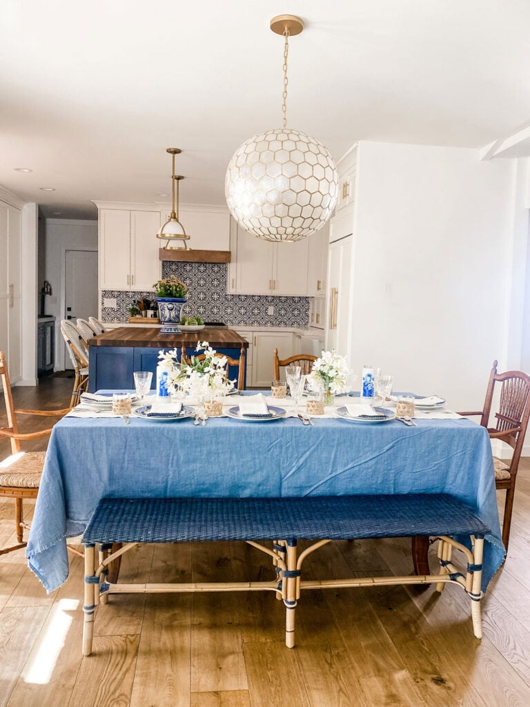 table with bench, chairs, pendant, blue tablecloth and blue and white tile