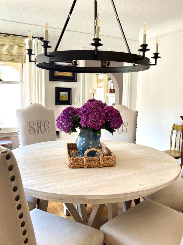 hydrangeas in blue pitcher in a sea grass tray on top of a round dining table with a chandelier