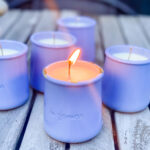 candles in periwinkle yogurt pots on wood table