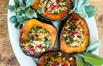 Vegan stuffed Acron squash with wild rice, dried cranberries, walnuts and herbs for a rustic colorful vegan thanksgiving side dish